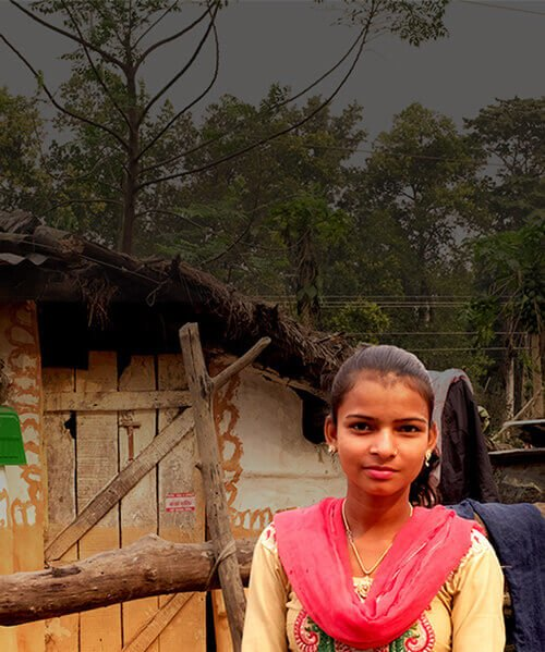 Young woman by shack in Nepal wearing red scarf