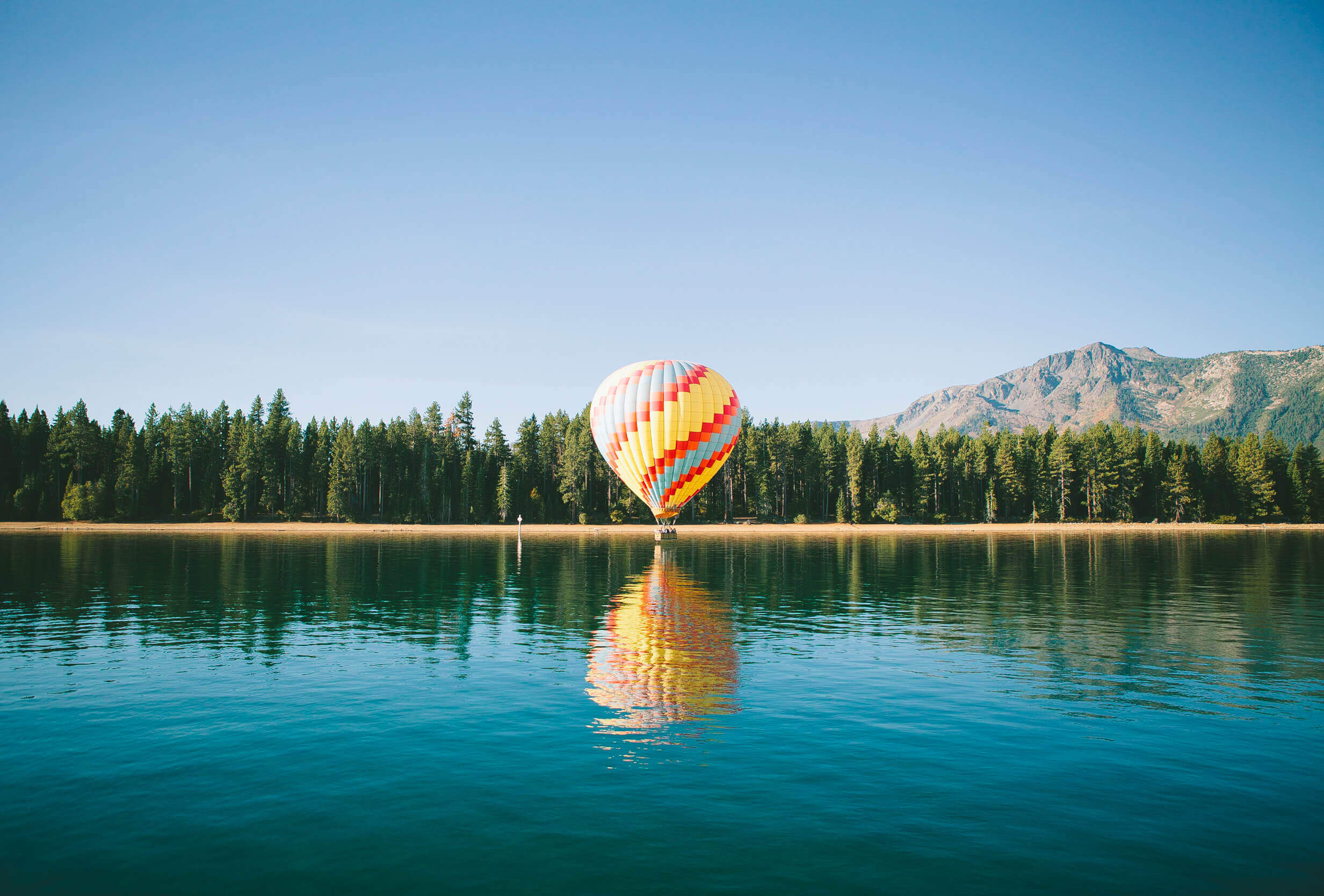 hot air balloon on water surrounded by moutains and evergreens
