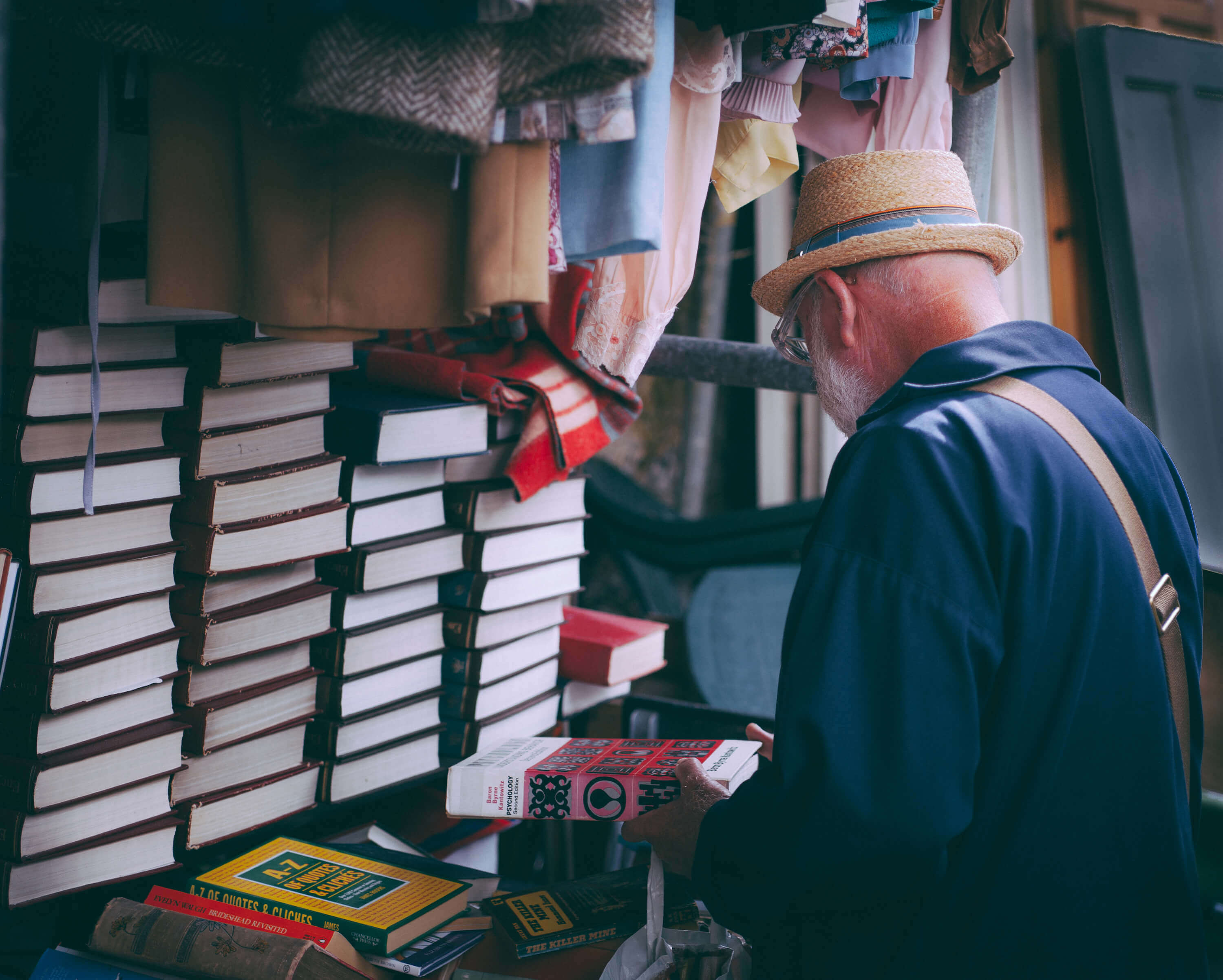 older man looking at books at a market