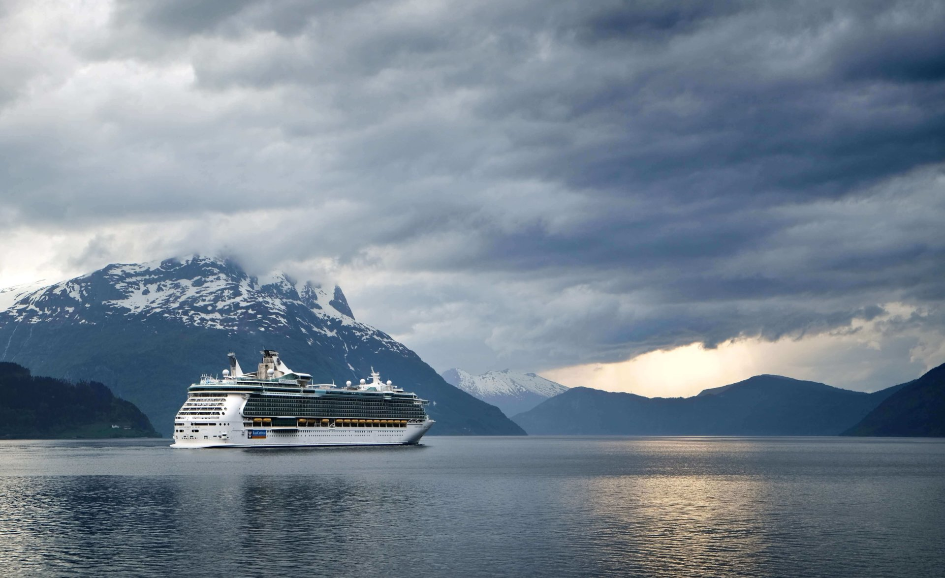 cruise ship on water surrounded by snow-capped mountains