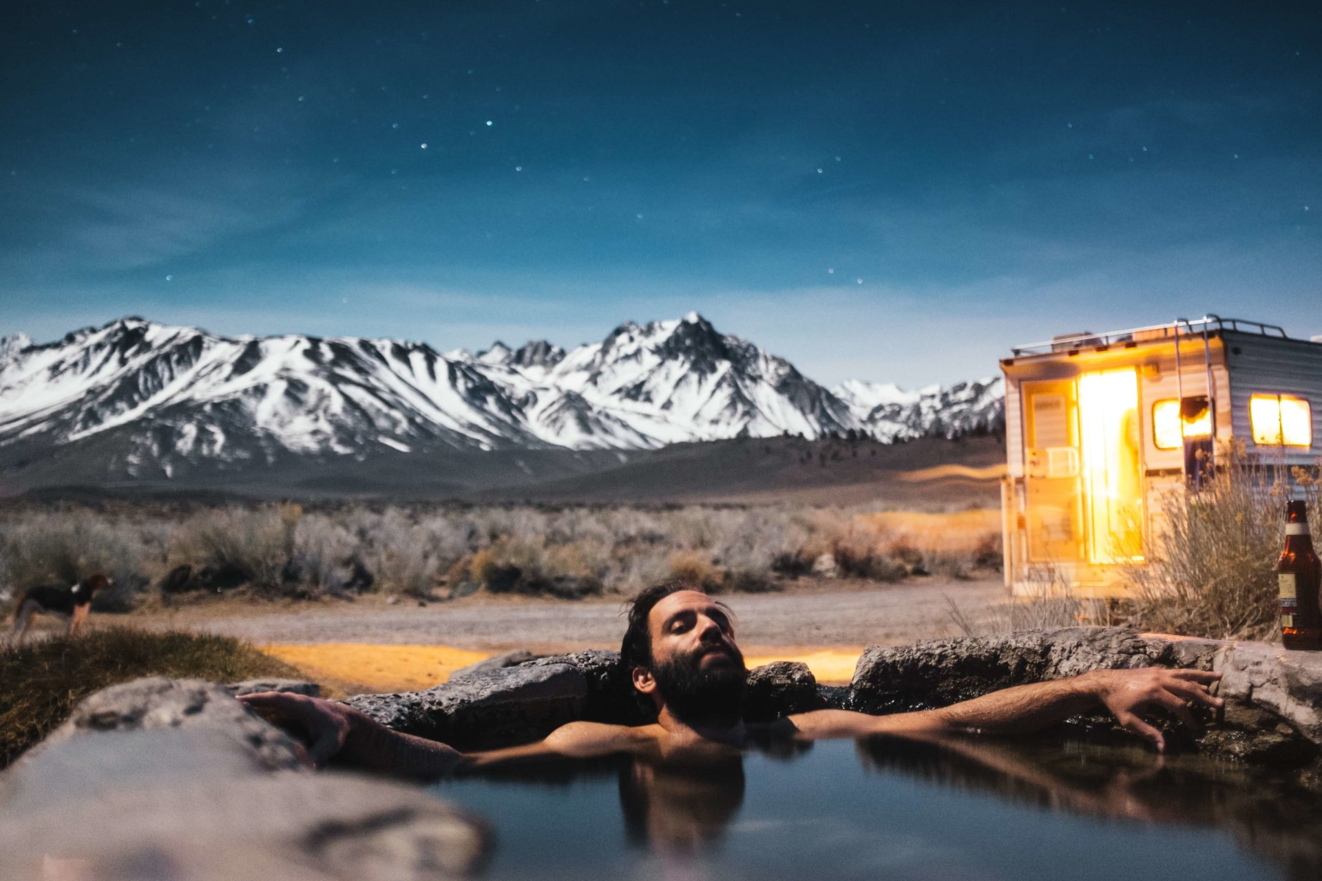 a man sitting in hot tub in wilderness under a starry night sky
