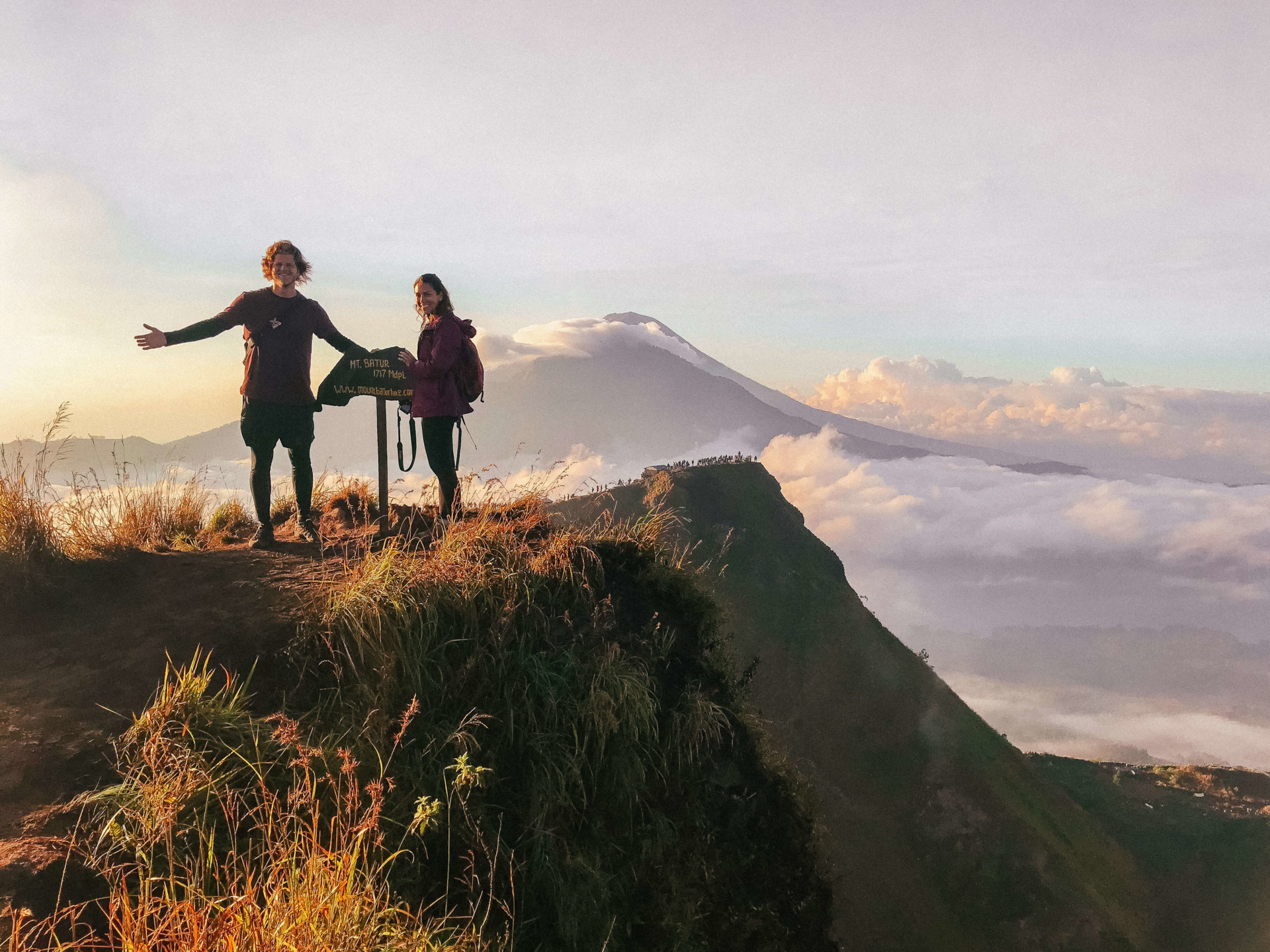 Double Occupancy standing on Mount Batur during sunrise