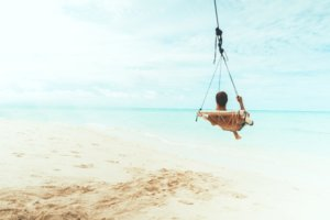 A man on a swing overlooking the ocean.