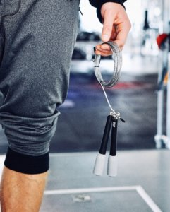 A man holding a jump rope in a gym.