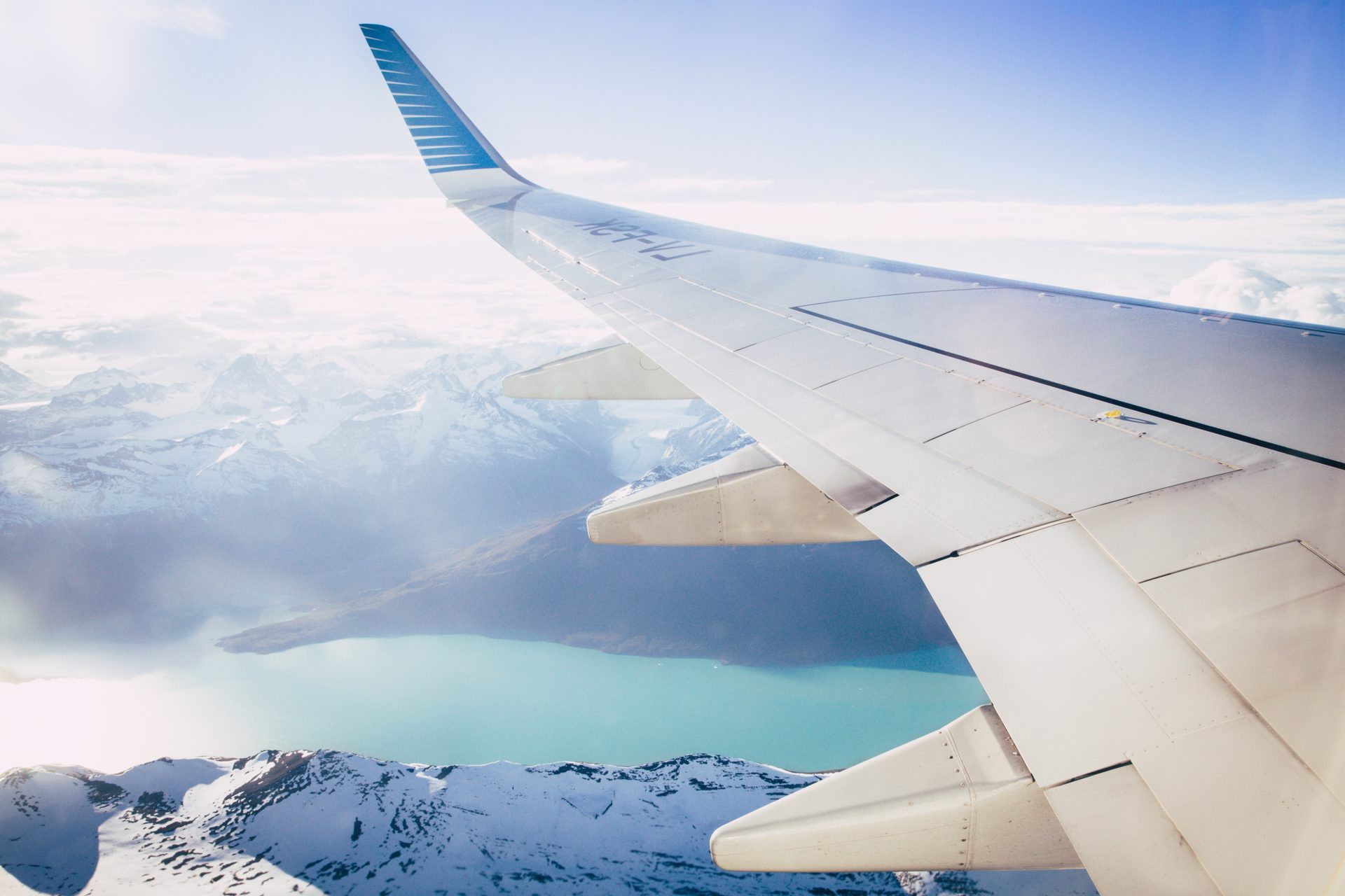 wing of plane over snow capped mountains and lake