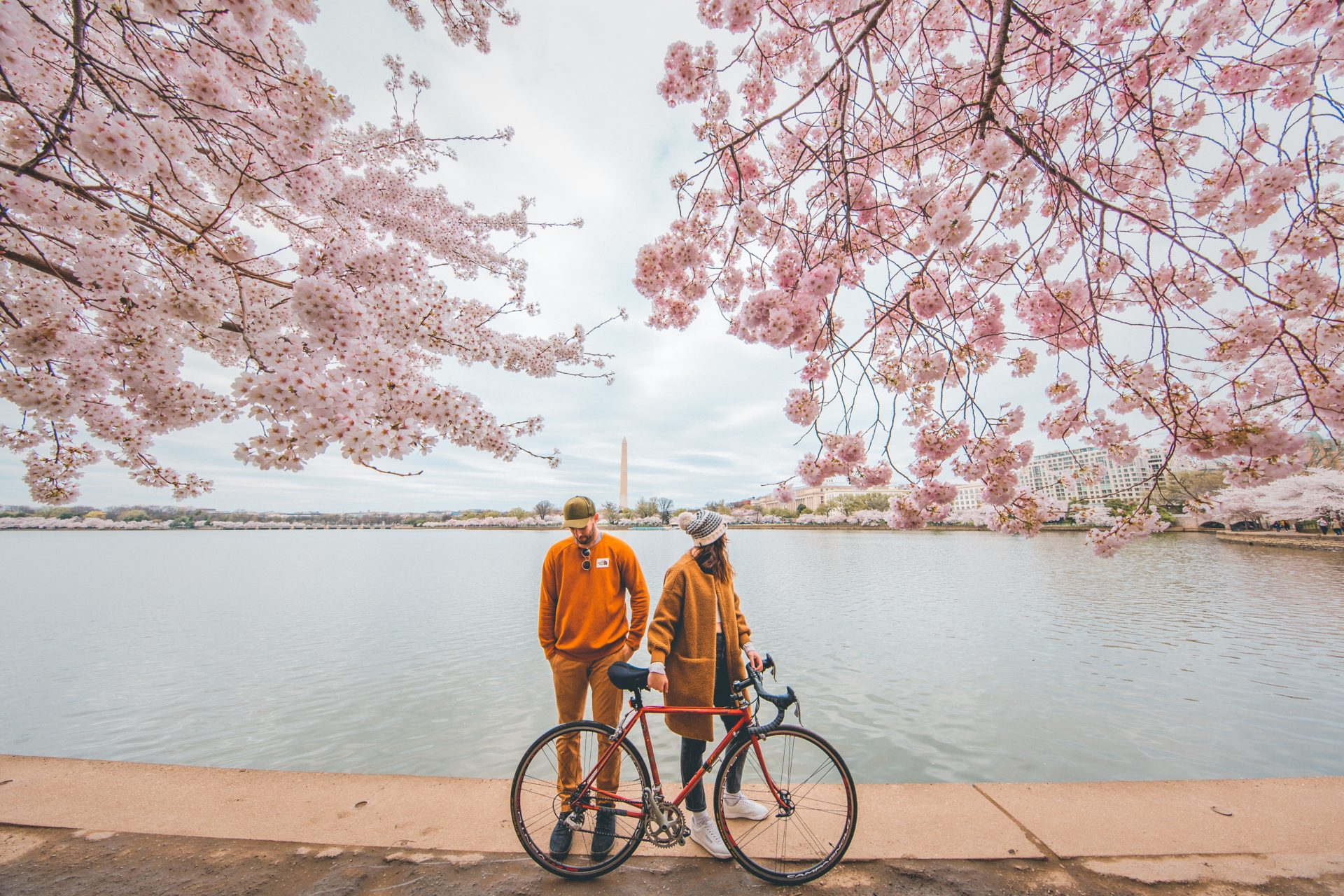 travel couple biking near water