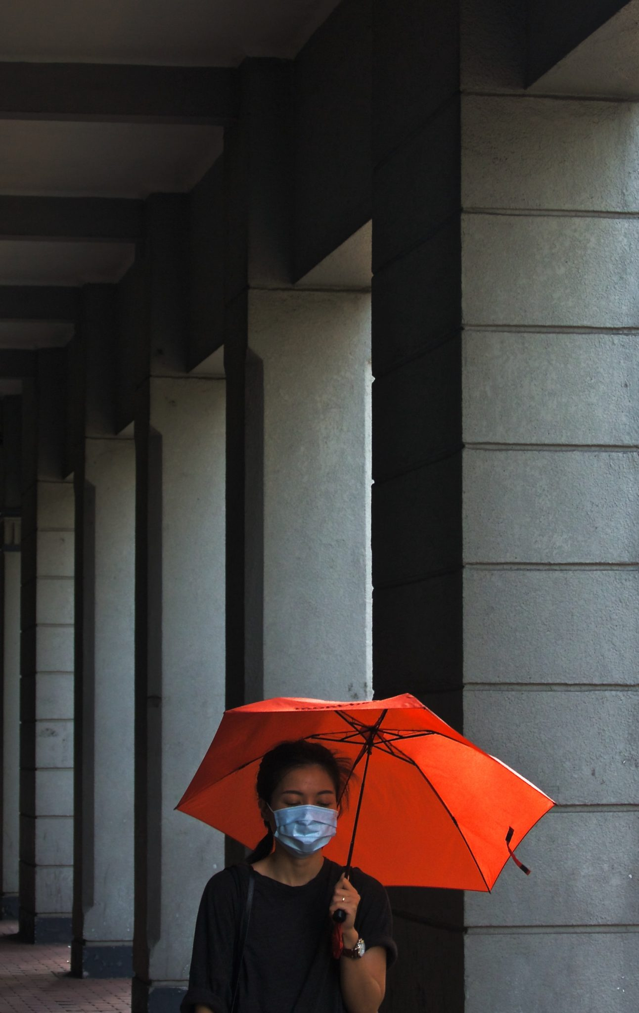 woman walking with umbrella during pandemic