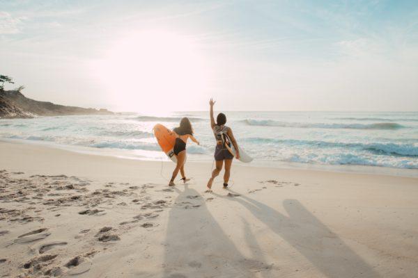 two women surfing near the ocean