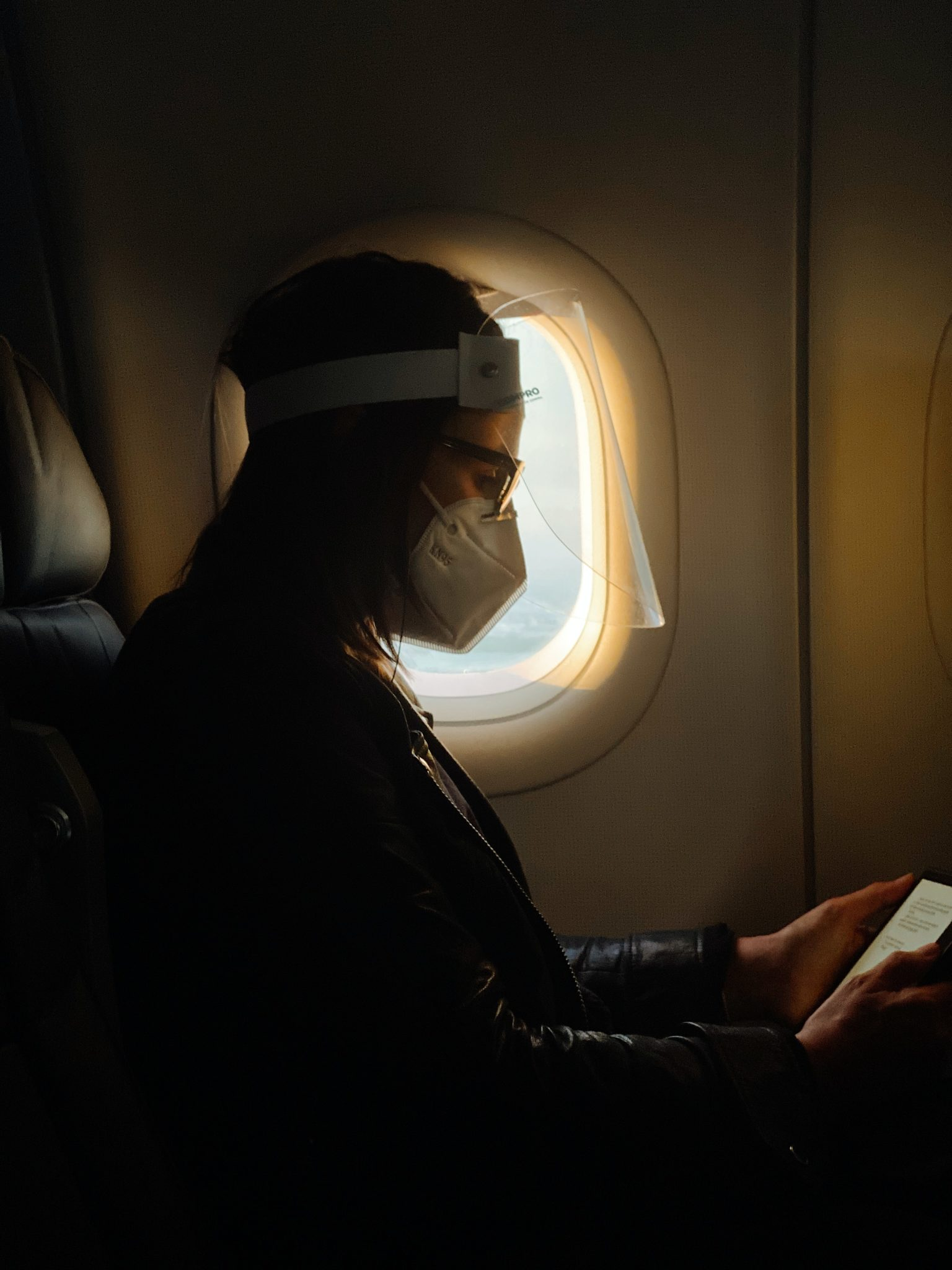woman with mask and face shield on airplane