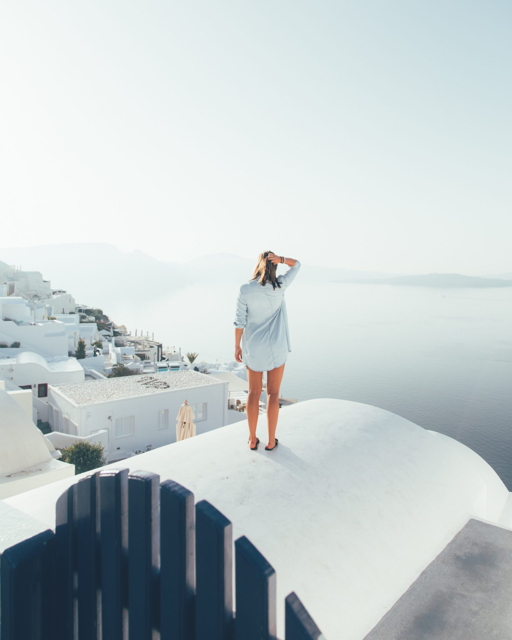 woman standing on top of building in santorini
